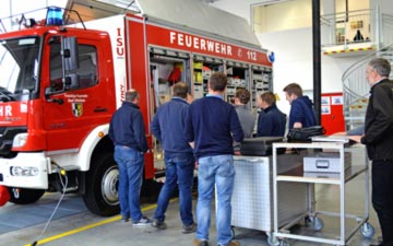 Feuerwehrleute vor Lentner-Fahrzeug